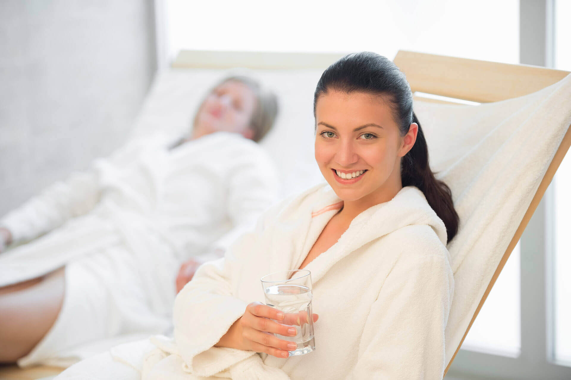 [object object] - smiling woman hold glass of water at beauty spa majestic 1 - Massage